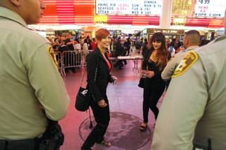 Anna Pokrovskaya, left, and Zlata Pavlova ask Metro officers if they can have a photo taken with them at the  Fremont Street Experience early Saturday, Oct. 5, 2013.