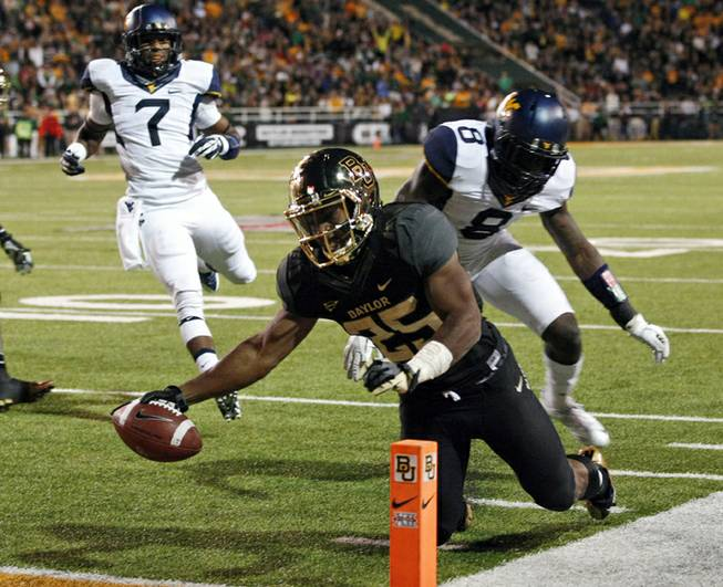 In this Oct. 5, 2013, file photo, Baylor running back Lache Seastrunk (25) scores past West Virginia safety Karl Joseph (8) during the first half of an NCAA college football game in Waco, Texas. Seastrunk boldly stated last year that he would win the 2013 Heisman Trophy, or come very close. Through four games, the former Oregon transfer is the nation's second-leading rusher in the 15th-ranked Bears' high-scoring offense.