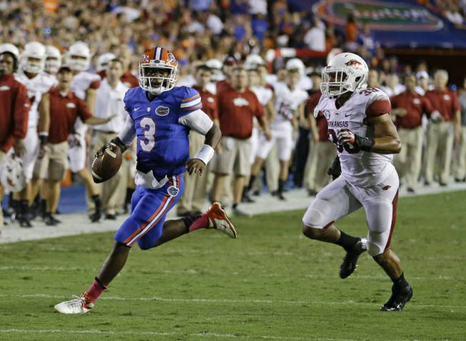Florida quarterback Tyler Murphy (3) looks for a receiver as he scrambles away from Arkansas linebacker Jarrett Lake, right, during the first half of an NCAA college football game in Gainesville, Fla., Saturday, Oct. 5, 2013.