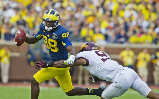 Michigan quarterback Devin Gardner (98) scrambles out of the pocket, defended by Minnesota linebacker James Manuel (9), in the third quarter of an NCAA college football game, Saturday, Oct. 5, 2013, in Ann Arbor, Mich. Michigan won 42-13.