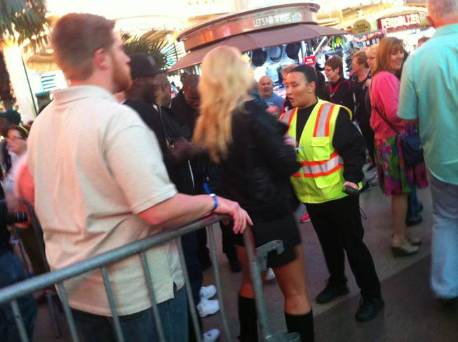 A woman waits for instructions from a security guard before passing a barricade at the Fremont Street Experiece on Friday, Oct. 4, 2013.