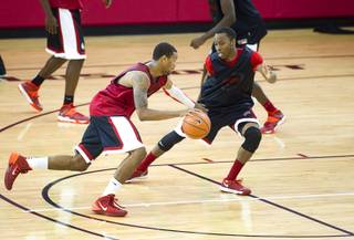 Bryce Dejean-Jones drives by Kevin Olekaibe during the first UNLV basketball practice of the season at UNLV's Mendenhall Center Monday, Oct. 7, 2013.