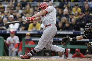 St. Louis Cardinals' Matt Holliday swings on a home run that scored Carlos Beltran in the sixth inning of Game 4 of a National League baseball division series against the Pittsburgh Pirates on Monday, Oct. 7, 2013, in Pittsburgh.
