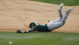 Oakland Athletics shortstop Jed Lowrie dives but is unable to stop the single by Detroit Tigers' Prince Fielder during the sixth inning of Game 3 of an American League baseball division series in Detroit, Monday, Oct. 7, 2013.