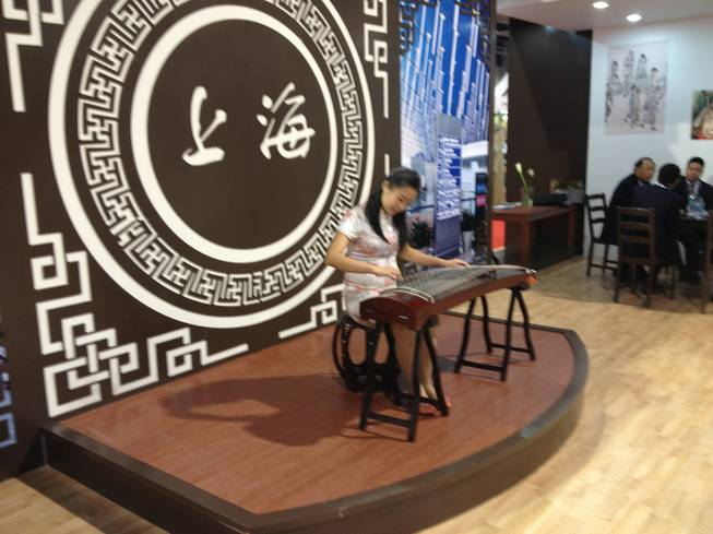 At Shanghai Pudong International Airports booth at World Routes 2013, a musician performed on a guqin on Oct. 7, 2013.