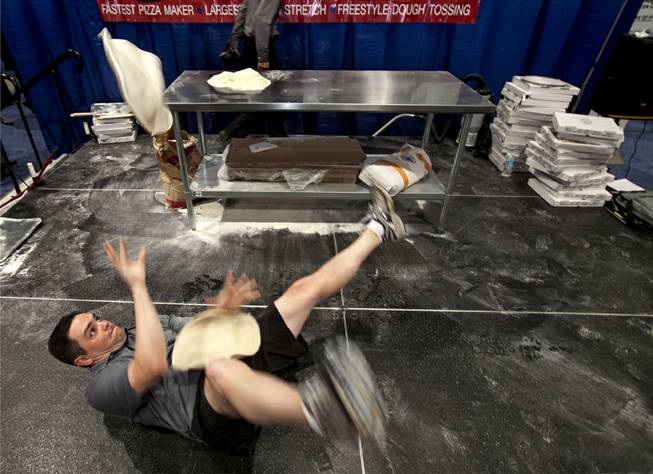 Dave Sommers of West Lafayette, Ind., hits the deck for some acrobatic practice following the day's competition during the International Baking Industry Exposition at the Las Vegas Convention Center.  As a member of the U.S. Pizza Team he's competed at the world championships in Parma, Italy and currently works for Mad Mushroom in West Lafayette.