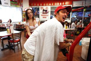 Reginaldo Tomitake of Brazil receives a spanking from waitress Jessica Diaz for not finishing his burger at the Heart Attack Grill in downtown Las Vegas on Tuesday, October 8, 2013.