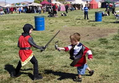 Brothers Jackson Reeves, 7, and Maddox Reeves, 3, battle near a food area during the Age of Chivalry Renaissance Festival in Silver Bowl Park on Sunday, Oct. 9, 2011.