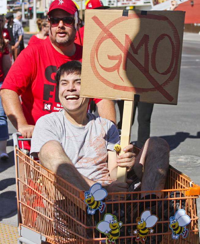 "Dale Andriaansen pushes Andrew Russell in a shopping cart during the ""March Against Monsanto"" protest opposing genetically modified food in downtown Las Vegas, Saturday, Oct. 12, 2013."