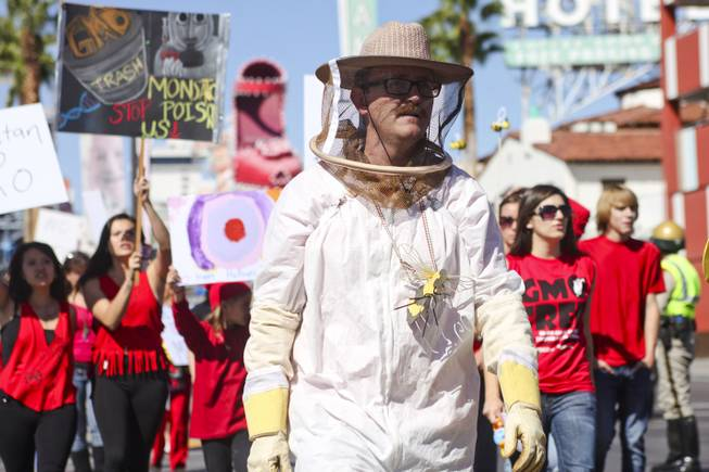 "A protester in a beekeeper outfit walks down Fremont Street during the ""March Against Monsanto"" protest opposing genetically modified food in downtown Las Vegas, Saturday, Oct. 12, 2013."