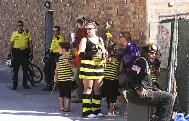 "Protesters dressed in bee costumes and bike cops gather behind Backstage Bar & Billiards on Fremont Street for the ""March Against Monsanto"" protest opposing genetically modified food in downtown Las Vegas, Saturday, Oct. 12, 2013."
