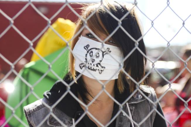 "A protester wears a mouth mask with a skull on it during the ""March Against Monsanto"" protest opposing genetically modified food in downtown Las Vegas, Saturday, Oct. 12, 2013."