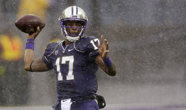 Washington quarterback Keith Price passes in the rain during the first half of an NCAA college football game against Arizona, Saturday, Sept. 28, 2013, in Seattle.