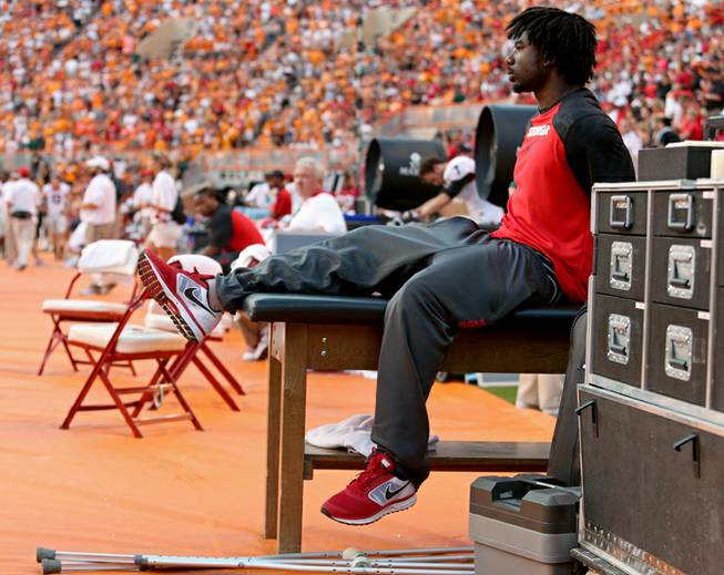 Georgia's Keith Marshall, right, sits on a training table during an NCAA college football game against Tennessee in Knoxville, Tenn., Oct. 5, 2013.