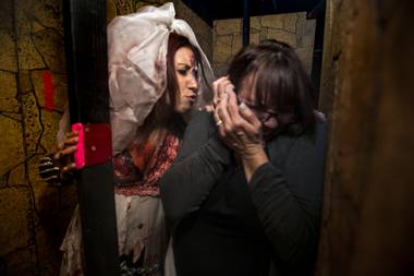 Succubus, left, works over a visitor at the Freakling Bros. Trilogy of Terror haunted house, Thursday, Oct. 10, 2013.