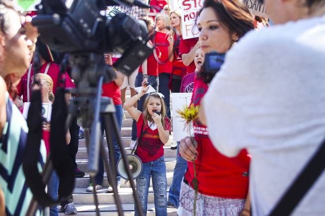 "A little girl yells into a megaphone outside the U.S. district courthouse during the ""March Against Monsanto"" protest opposing genetically modified food in downtown Las Vegas, Saturday, Oct. 12, 2013."