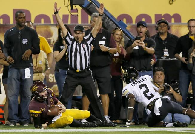 Arizona State's Taylor Kelly, bottom left, hangs on to the football as he beats Colorado's Kenneth Crawley (2) to the end zone as field judge Steven Strimling signals for the touchdown during the first half of an NCAA college football game on Saturday Oct. 12, 2013, in Tempe, Ariz.