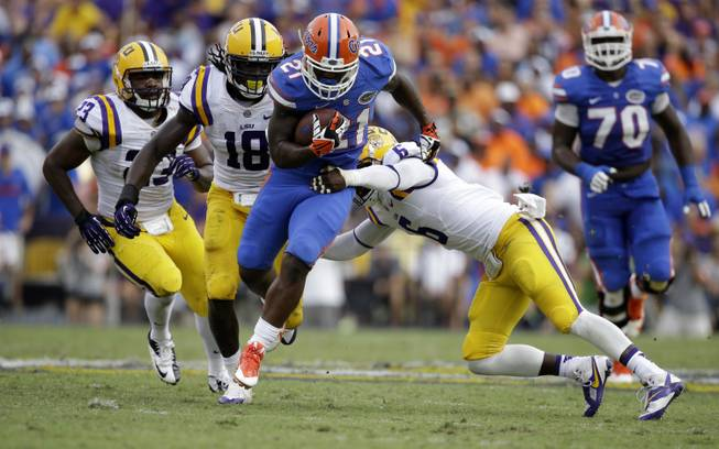 Florida running back Kelvin Taylor (21) carries as  safety Craig Loston (6) tries to tackle with linebacker Lamin Barrow (18) and linebacker Lamar Louis (23) pursuing in the second half of an NCAA college football game in Baton Rouge, La., Saturday, Oct. 12, 2013.  LSU won 17-6.
