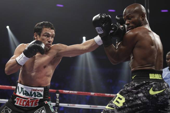 Juan Manuel Marquez, left, of Mexico, punches at WBO welterweight champion Timothy Bradley Jr. of the U.S during their title fight at the Thomas & Mack Center in Las Vegas, Nevada, Oct. 12, 2013.