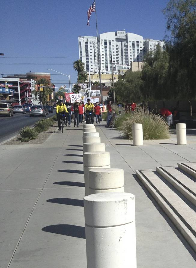 Metro Police officers lead anti-GMO marchers to the U.S. district courthouse steps in downtown Las Vegas on Saturday, Oct. 12, 2013.