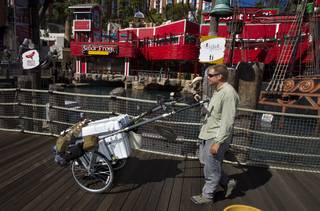 """The Walking Man"" Karl Bushby makes his way along Las Vegas Boulevard South past Treasure Island on Monday, Oct. 14, 2013, with his cart ""The Beast"" on his way to Caesars Palace for a three-day stay."