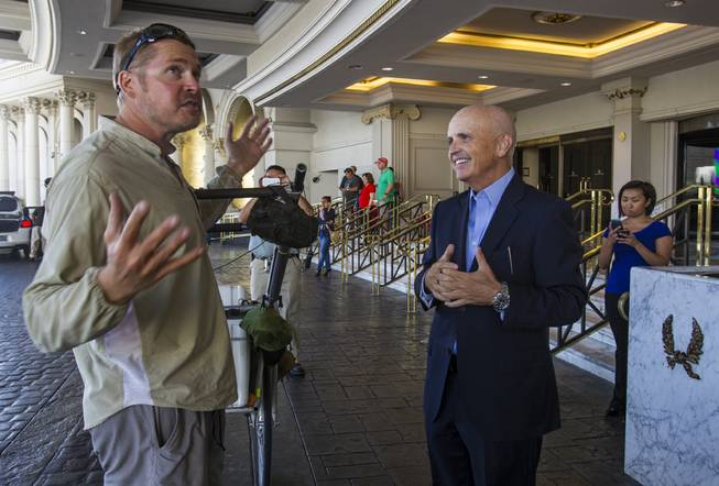 "Gerald Tuthill, assistant general manager of Caesars Palace, greets ""The Walking Man"" Karl Bushby on Monday, Oct. 14, 2013, outside Caesars."