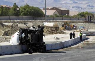 Nevada Highway Patrol troopers and investigators look over the scene of a fatal crash involving a cement truck on the northern 215 beltway near Jones Boulevard Tuesday, Oct. 15, 2013. The accident has closed the beltway in both directions between Jones Boulevard and Sky Pointe Drive.