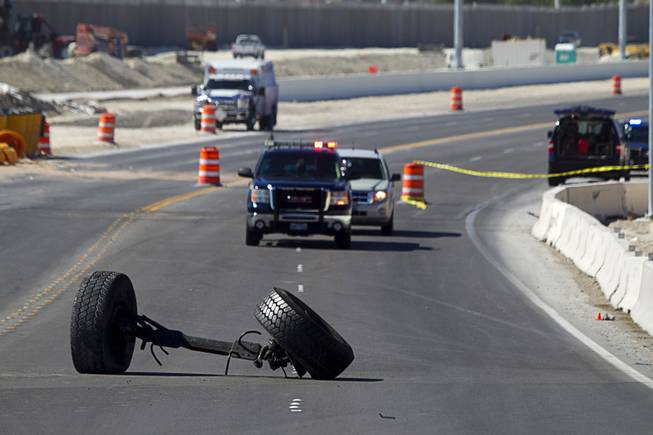 The front axle of a cement truck is shown in the roadway at the scene of a fatal crash on the northern 215 beltway near Jones Boulevard Tuesday, Oct. 15, 2013. The accident has closed the beltway in both directions between Jones Boulevard and Sky Pointe Drive.