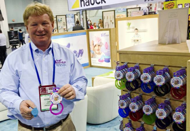Lee Bowen, vice president of operations for Kid Kusion, holds up items from their Gummi teething jewelry line at the ABC Kids Expo at the Las Vegas Convention Center, Tuesday, Oct. 15, 2013.