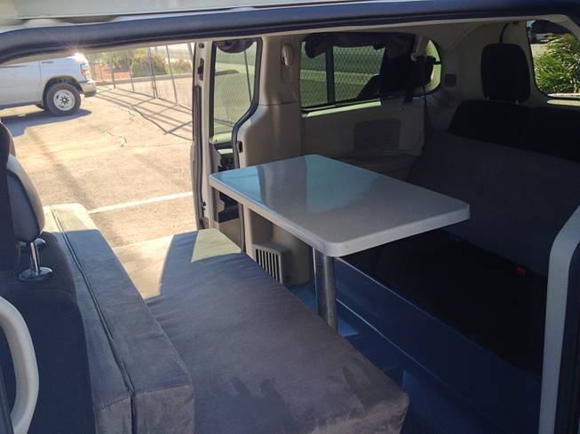 The interior of the van has a kitchen table with bench seats that convert into a double bed.