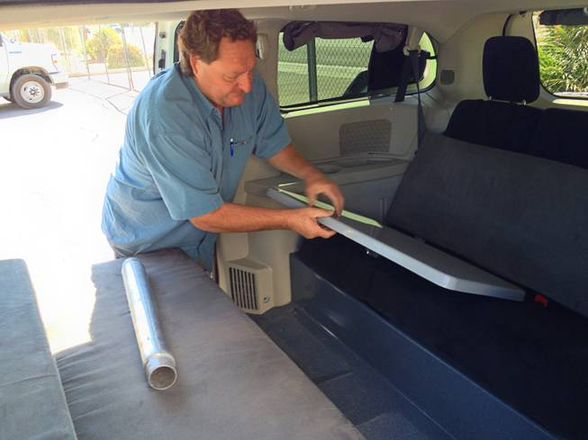 Kurt Luthy of Apollo converts the kitchen table into the double bed, removing the pole holding the table and sliding the table to support the mattress. .
