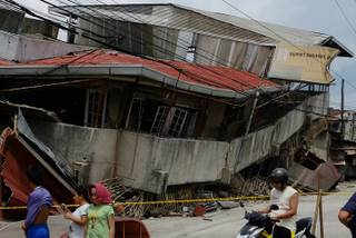 Residents walk past a damaged structure in Cebu, central Philippines on Tuesday Oct. 15, 2013. A 7.2-magnitude earthquake struck in the central Philippines on Tuesday morning, collapsing roofs and buildings, cracking walls and roads and killing several people.