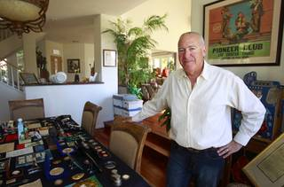 Steve Cutler poses by a small sampling of his collection of Las Vegas memorabilia at his home Wednesday, Oct. 16, 2013. Cutler, founder of Casino Legends Hall of Fame, used to display his collection in a museum at the Tropicana but is now looking for a new way to display the collection.