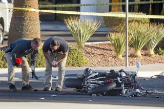 Metro Police investigators look over an accident scene after a fatal motorcycle accident on West Sahara Avenue near Buffalo Drive Wednesday, Oct. 16, 2013.
