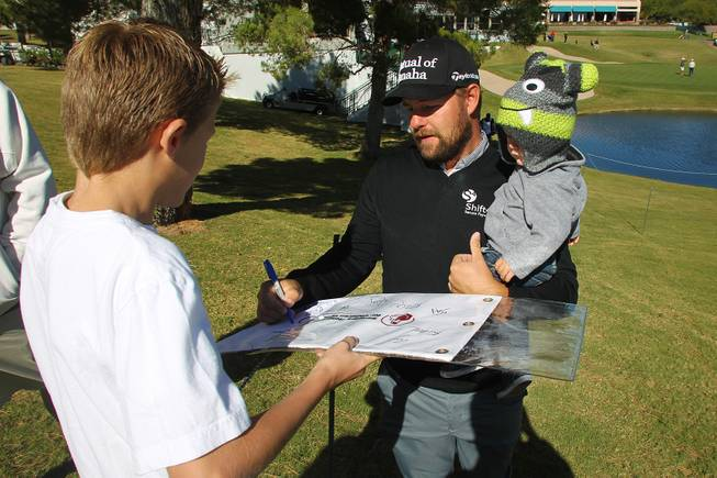 Holding his son Tucker, Ryan Moore signs an autograph during the Shriners Hospital for Children Open pro-am tournament Wednesday, Oct. 16, 2013.