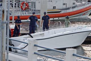 U.S Coast Guard personnel inspects a vessel with a missing center console that capsized near Miami,  Wednesday Oct. 16, 2013.  The Coast Guard responded to an early morning call and found nine people clinging to the hull seven miles east of Miami.  Four women died and 10 other people were taken into custody after the boat with more than a dozen people aboard, including Haitian and Jamaican nationals, capsized in the waters off South Florida.  Authorities are investigating whether the victims and survivors were part of a human smuggling operation.