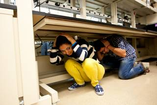 Jasmine Badizadeh and Abner Mivakhorli, right, cover their heads while seeking shelter under a desk during the Great Nevada ShakeOut earthquake drill held in the Applied Geophysics Center at UNLV at 10:17 a.m. Thursday morning in Las Vegas, October 17, 2013.