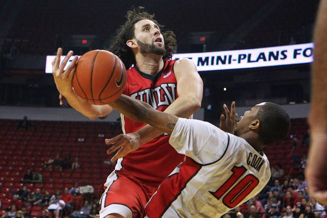 UNLV forward Carlos Lopez Sosa is fouled by guard Daquan Cook during their annual preseason Scarlet and Gray scrimmage Thursday, Oct. 17, 2013 at the Thomas & Mack.