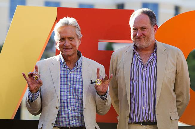 "Actor Michael Douglas, left, and director Jon Turteltaub pose during a ceremony for cast members of ""Last Vegas"" in front of the Bellagio Friday, Oct. 18, 2013. Douglas is holding ""gaming chips"" from Clark County and the Las Vegas mayor's office. Las Vegas Mayor Carolyn Goodman and Clark County Commission Chairman Steve Sisolak declared Oct. 18, 2013 to be ""Last Vegas Day"" in Las Vegas and Clark County. The movie by CBS Films opens nationwide on November 1."