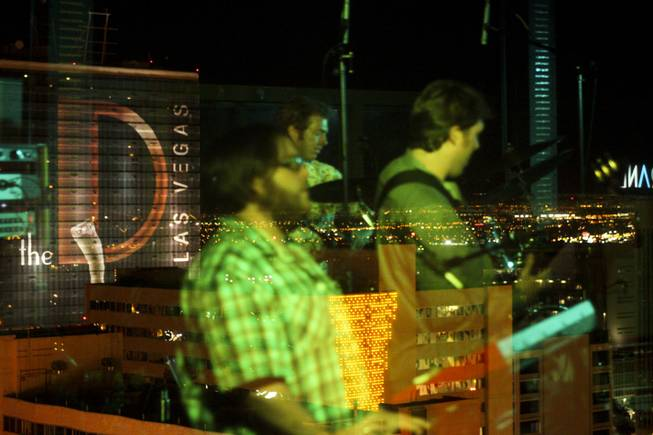 "Local band Moksha is reflected off the rooftop glass wall during their set at the ""Rooftop Fall Ball 3"" at Binion's Gambling Hall & Hotel pool deck, Friday, Oct. 18, 2013."