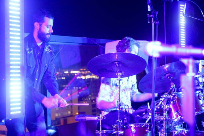 "Sam Lemos jumps on the cow bell with drummer Pat Gray during their band, Moksha's, set at the ""Rooftop Fall Ball 3"" on the Binion's Gambling Hall & Hotel rooftop pool deck, Friday, Oct. 18, 2013."
