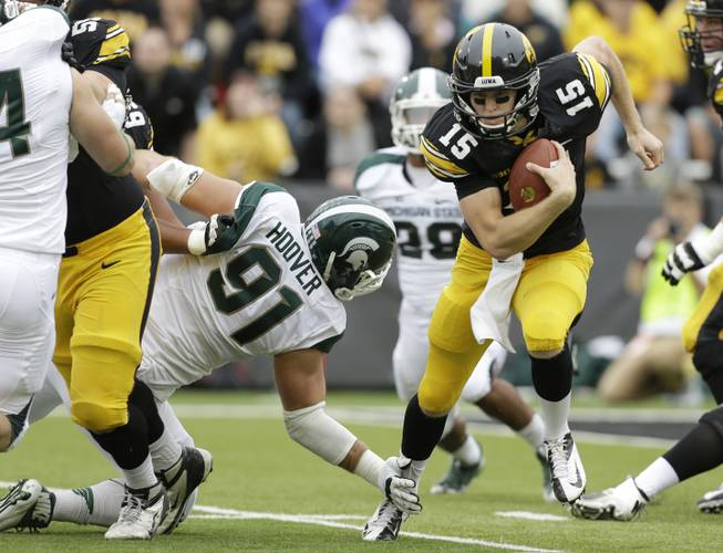 Iowa quarterback Jake Rudock (15) runs from Michigan State defensive tackle Tyler Hoover (91) during the first half of an NCAA college football game, Saturday, Oct. 5, 2013, in Iowa City, Iowa.