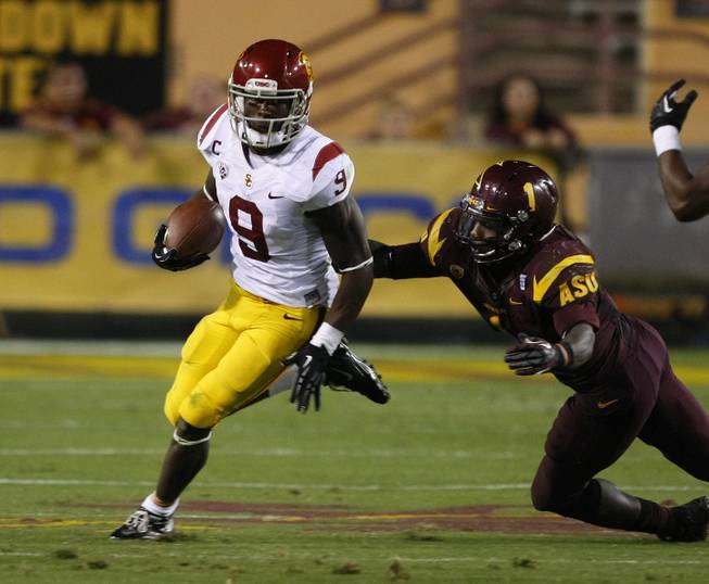 Southern California wide receiver Marqise Lee (9) gets tackled by Arizona State Marion Grice (1) during the second half of an NCAA college football game on Saturday, Sept. 28 2013, in Tempe, Ariz. Lee was hurt on the play and never returned to the game.