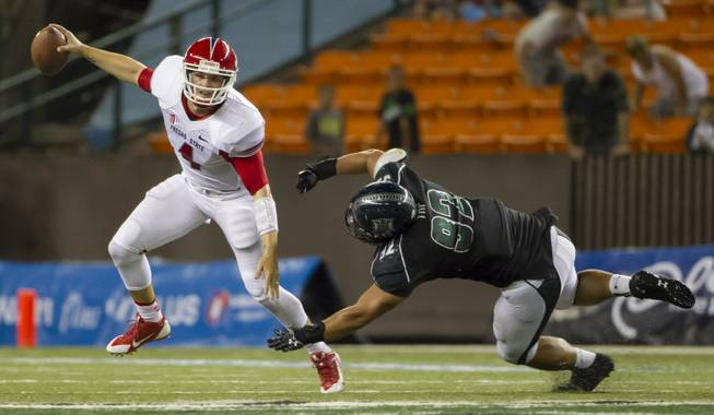 Fresno State quarterback Derek Carr, left, escapes from Hawaii defensive lineman Beau Yap in the fourth quarter on Saturday, Sept. 28, 2013, in Honolulu. Fresno State held off Hawaii 42-37.
