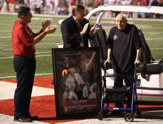 Fresno State University President Joseph Castro and Athletic Director Thomas Boeh applaud Fresno State alumni Jerry Tarkanian during the first half of an NCAA college football game Saturday, Oct. 19, 2013, in Fresno, Calif. (AP Photo/Gary Kazanjian)