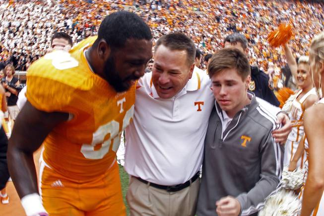 Tennessee head coach Butch Jones, center, celebrates with Tennessee defensive lineman Malik Brown (90) and his son, Alex Jones, after defeating South Carolina 23-21 in an NCAA college football game on Saturday, Oct. 19, 2013 in Knoxville, Tenn.