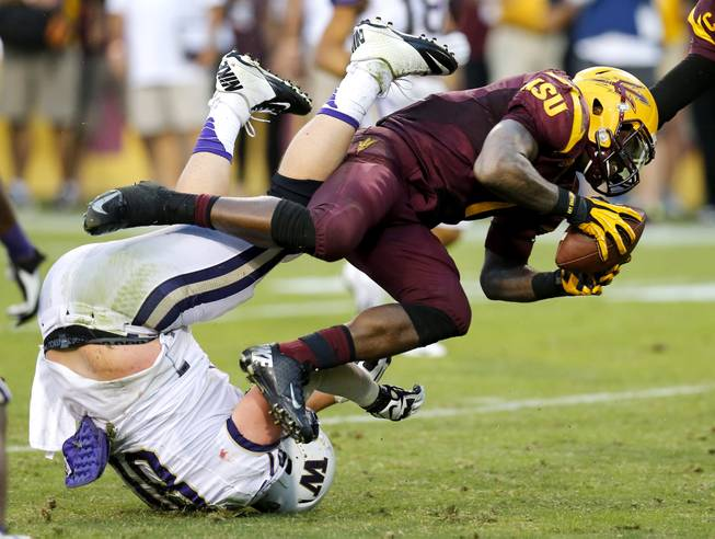 Arizona State running back Marion Grice (1) knocks over Washington defensive end Evan Hudson, left, during the second half of an NCAA college football game, Saturday, Oct. 19, 2013, in Tempe, Ariz. Arizona State won 53-24.