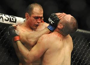 Former heavyweight champion Junior Dos Santos, left, and UFC heavyweight champion Cain Velasquez  fight for the UCF World Heavyweight title in Houston, Saturday, Oct. 19, 2013. Velasquez kept his title, beating Santos with a TKO in the fifth round. (AP Photo/Pat Sullivan)