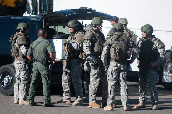 Swat team members secure the scene near Sparks Middle School in Sparks, Nev., after a shooting there on Monday, Oct. 21, 2013.  Authorities are reporting that two people were killed and two wounded at the Nevada middle school.