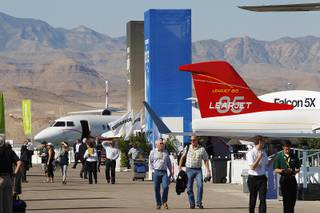 Attendees walk among aircraft during a static display of jets at the Henderson Executive Airport Tuesday, Oct. 22, 2013 as part of the National Business Aviation Association convention.